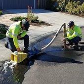 two crew members flush water main on cul-de-sac