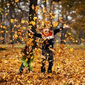 children playing in leaves outside