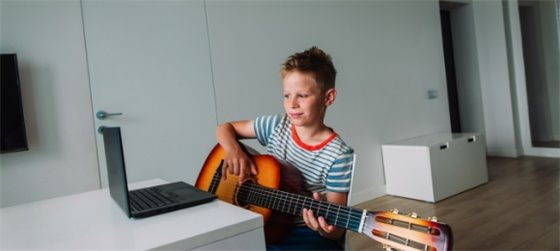 boy plays guitar as part of online classes - registration now open