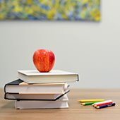 apple sitting on a stack of books next to pencils on a desk