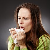 woman coughing into a disposable tissue
