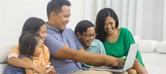 Family sits on the couch and enjoys free virtual community events via laptop