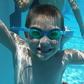 young boy in goggles smiles underwater in swimming pool