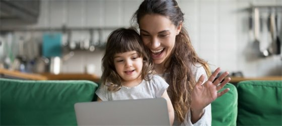 Mother and daughter enjoy virtual activities in front of a laptop screen