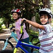 Thumbnail--One-male-and-one-female-student-with-helmets-on-bikes