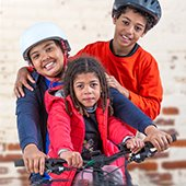 three-children-wearing-jackets-and-helmets-with-a-bicycle