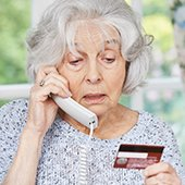 older-adult-woman-victim-of-phone-scam-holding-credit-card