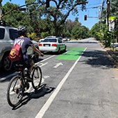 student rides bicycle in bike lane