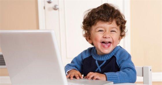 Preschooler laughing in front of computer