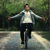 young-man-riding-bicycle-hands-free