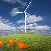 Wind power generating turbine with California poppies in the foreground