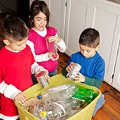 three-children-kneeling-around-a-recycle-bin-sorting