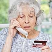 old lady on phone holding credit card scam victim