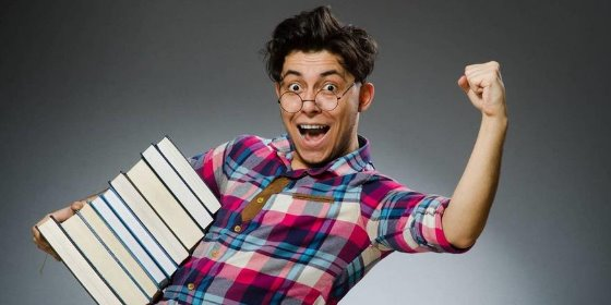 man holding a large stack of books