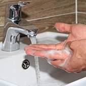 man's hands washing with soap under running faucet