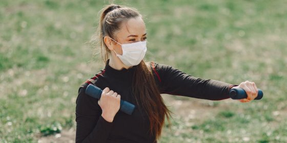 woman wears a mask while working with weights outside