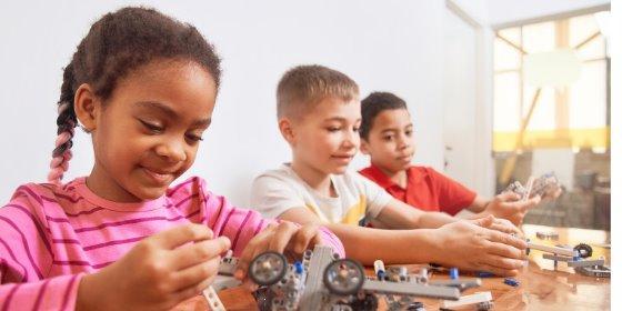 three children work on a robotics project