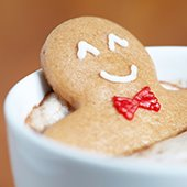 Gingerbread man sitting in cup of hot cocoa