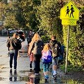 Parents walk children to school through puddles on wet street