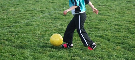 Child playing soccer on a grass field