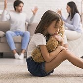 young girl holds teddy bear as parents argue in the background
