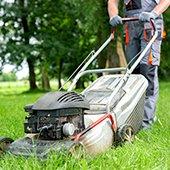 man pushing lawnmower through tall grass