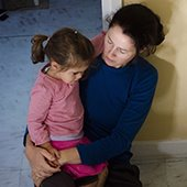 immigrant mother and daughter sitting on kitchen floor