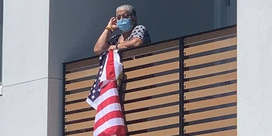 african-american-woman-holding-an-American-flag-from-balcony