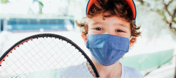 young boy wearing face mask holding tennis racket for featured outdoor activity - tennis