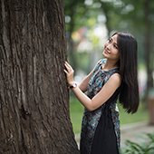 thumbnail--young asian woman standing next to a tree trunk