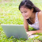 thumbnail--girl-uses-laptop-outdoors-on-lawn