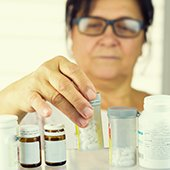 woman looking at prescription bottles for medical disposal