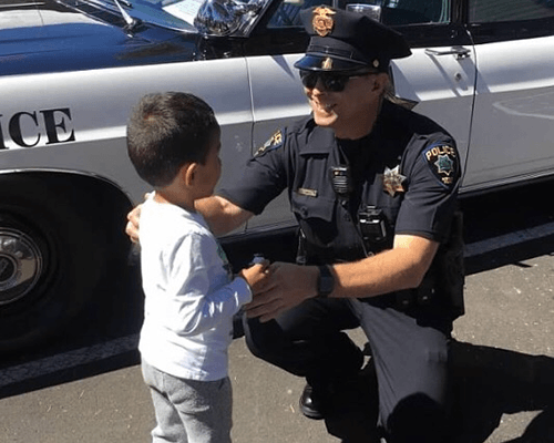An officer kneels to greet a young boy at a community event.