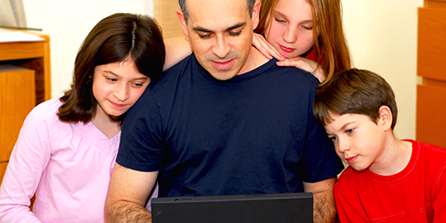 Blog-post--Father-two-daughters-and-son-looking-at-laptop