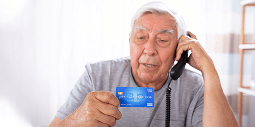 Blog-post--older-adult-hispanic-man-on-phone-holding-credit-card---scam