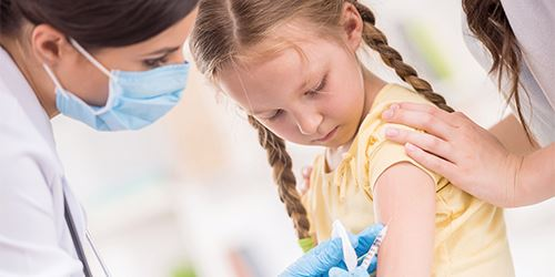 Blog--Parent-comforts-child-who-receives-flu-shot-from-medical-professional